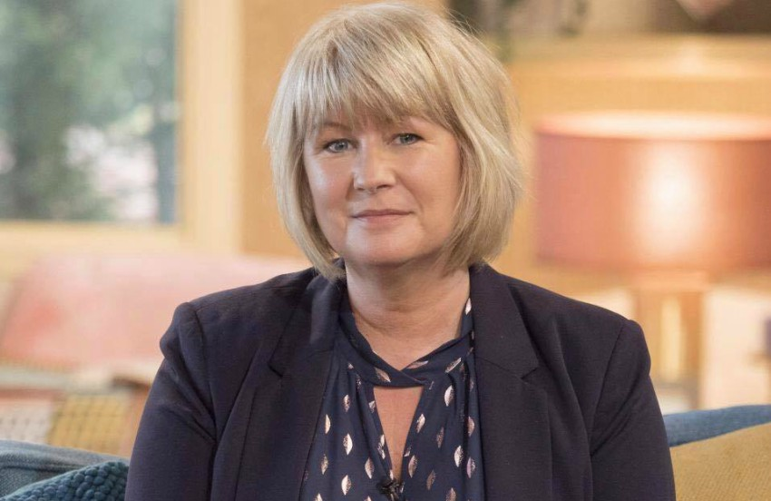 a headshot of susie green who has bob length blond hair and is wearing a black blazer