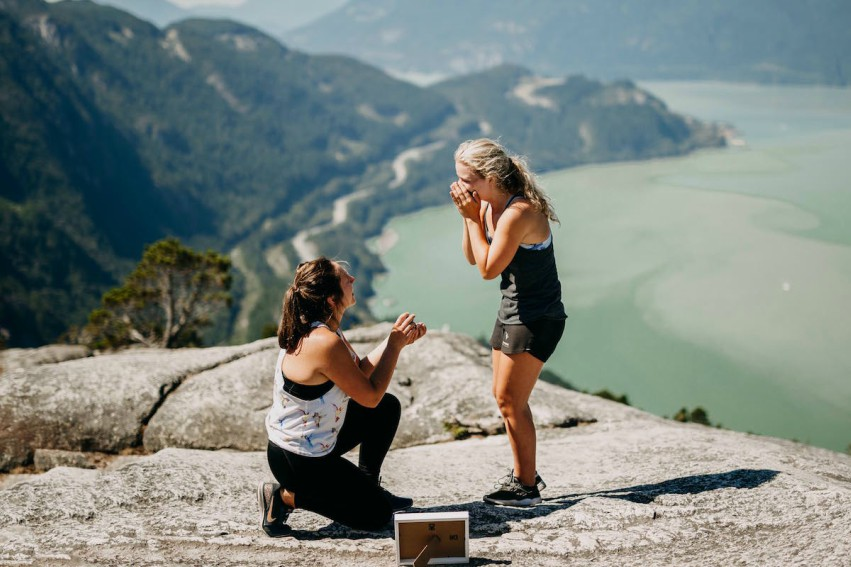 two women on a cliff top in active, one woman is on her knees proposing to the other one