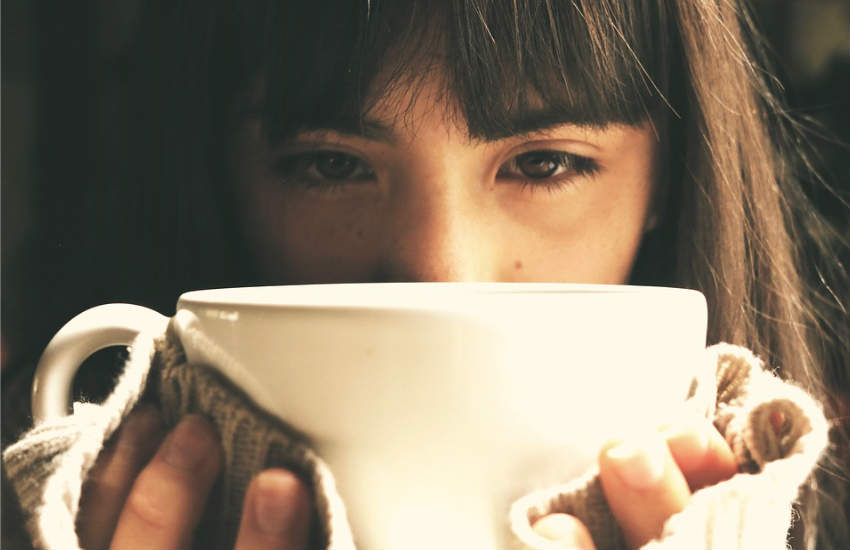 A closeup of a girl looking sad and holding a mug in her hands.