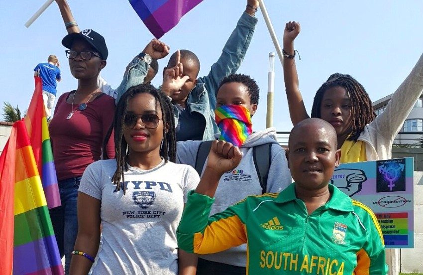 a group of people standing together smiling and holding rainbow flags, some have their hands in the air, one is wearing a sports top reading south africa
