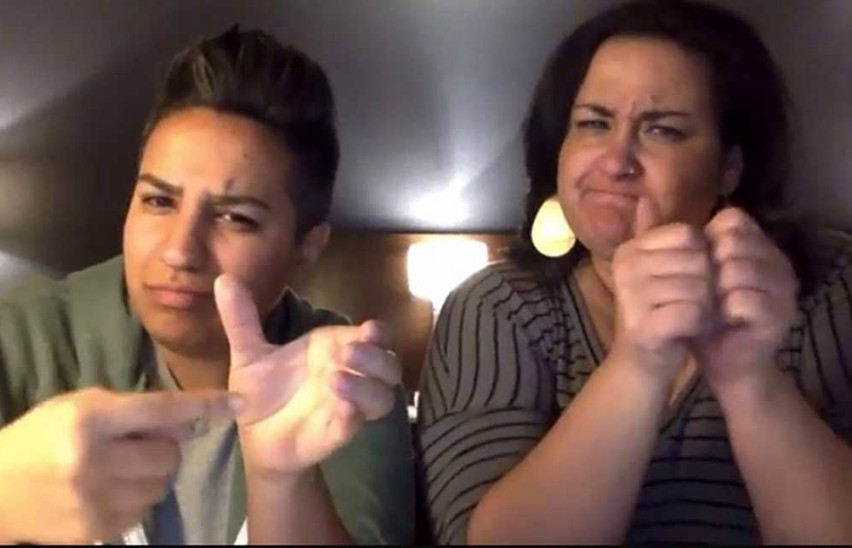 two women doing sign language into a camera