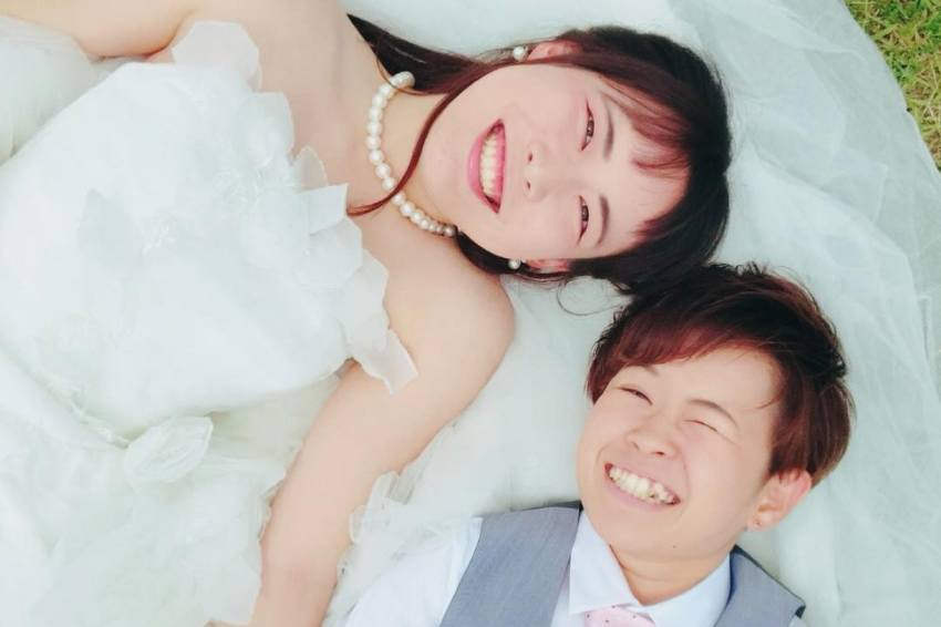a couple lying on their backs in wedding attire looking up at the camera. they are both women, one is wearing a traditional white wedding dress, while the other is in a grey vest pink tie and white shirt