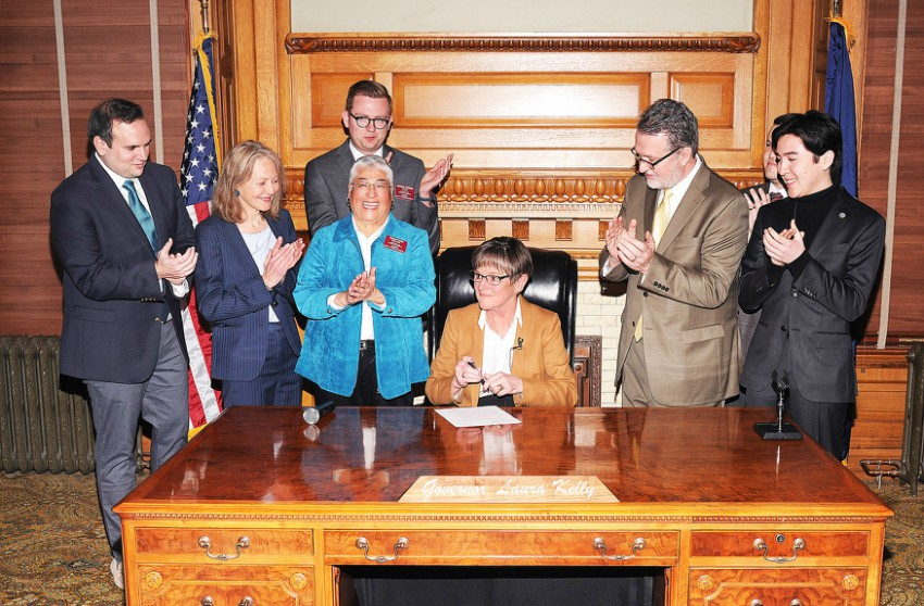 a woman sits a big wooden desk signing a paper surrounded by people clapping