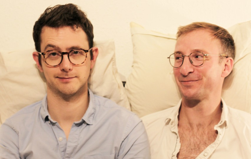 two men sitting in a bed with a pillow behind them. they're both wearing shirts and glasses. the man on the right is looking at the other man