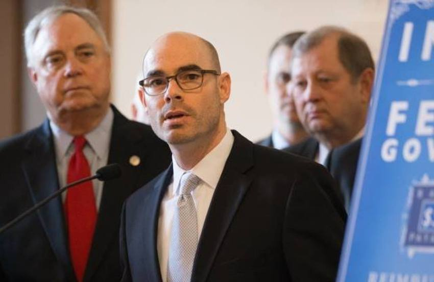 Dennis Bonnen wearing a dark suit speaking at a lectern, there are a lot of white men in suits standing behind him