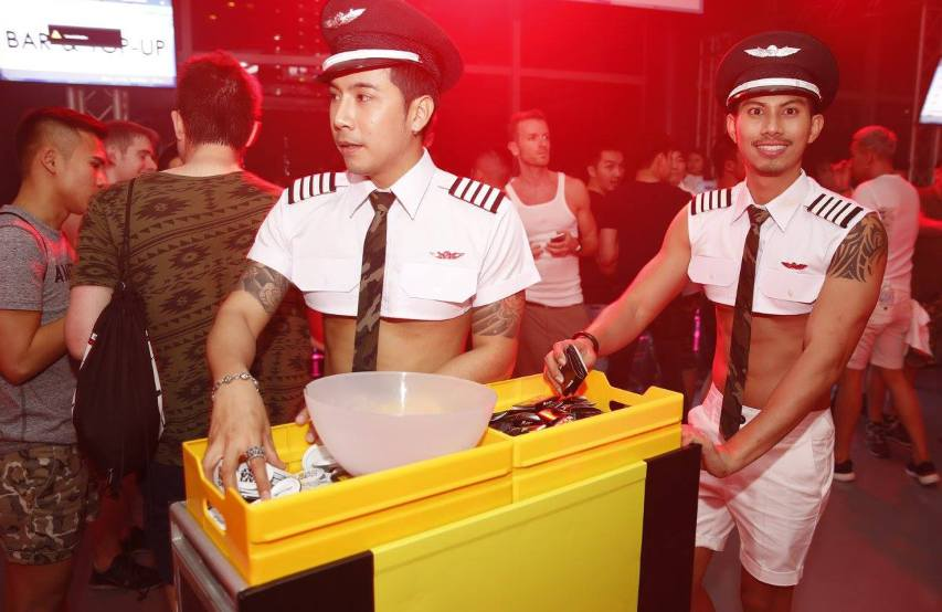 two men in skimpy flight attendant uniforms hand out condoms