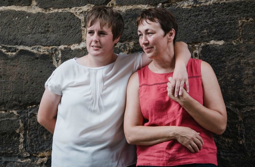 two women standing against a stone brick wall, one woman in a white top has her arm over the shoulder of the other woman in a pink top. they both have short hair