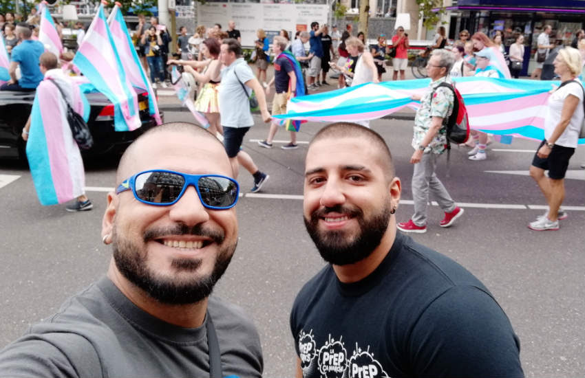 Two men taking a selfie at a Pride parade. In the background, people marching waving trans flags.