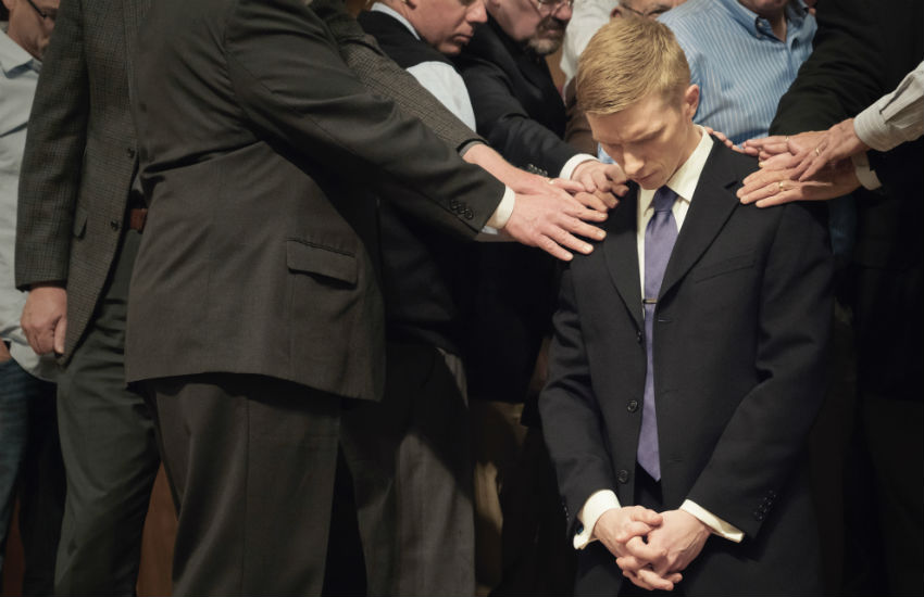 A man is prayed over in church by Evangelicals