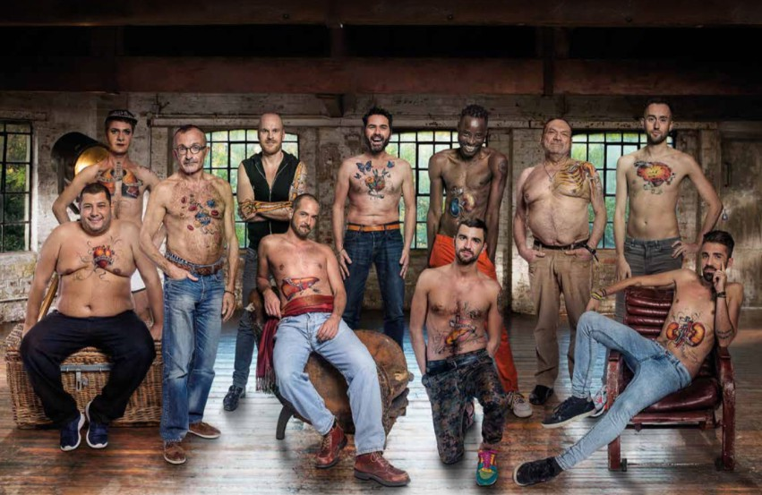 a group of men standing in a warehouse, topless with body parts painted on their torsos