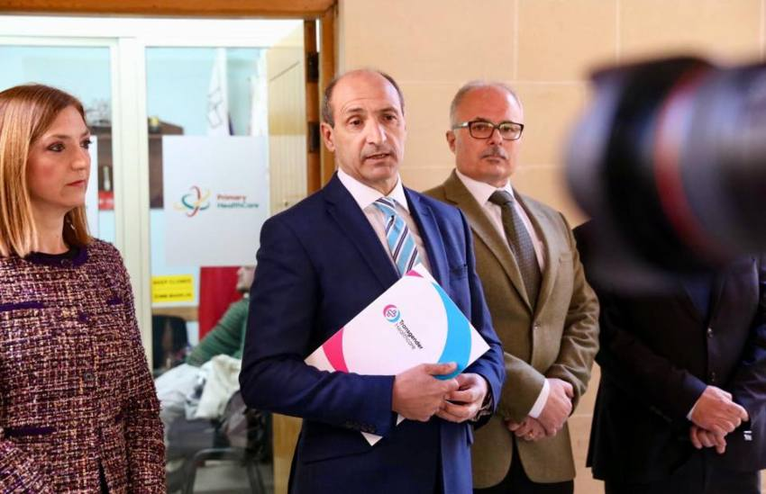 Chris Fearne address media holding a policy document at the new gender clinic
