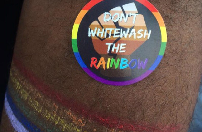 a sticker on a man's arm that has a fist in brown and black colours that reads 'don't whitewash the rainbow'