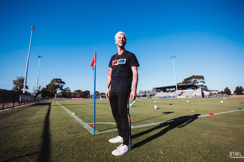 a man with bleach blond hair standing on the edge of a soccer pitch