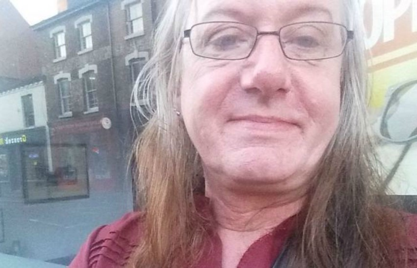 a selfie of a middle aged woman standing on a public street,she is wearing glasses