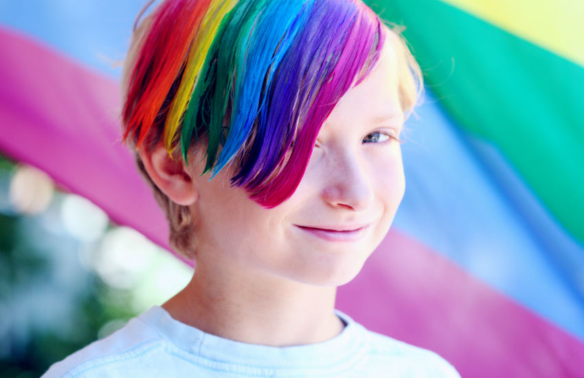 A young person with rainbow colored hair against a rainbow flag