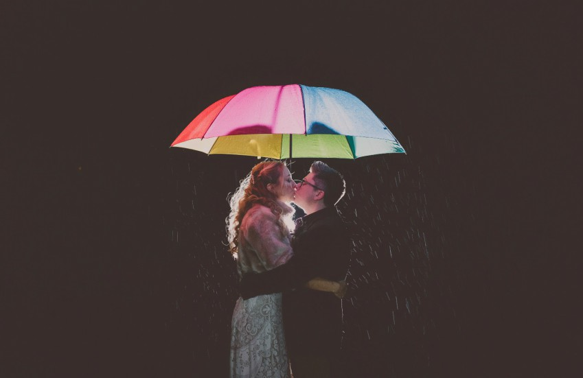 a couple stands under a lit up rainbow coloured umbrella and they are kissing. they are wearing wedding attire