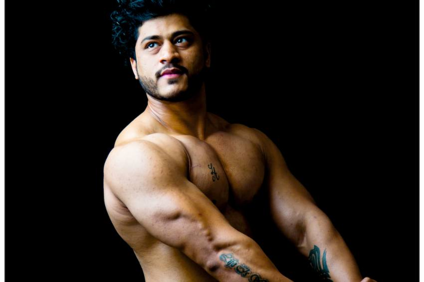 a topless man with big muscles poses with his arms stretched in front of him
