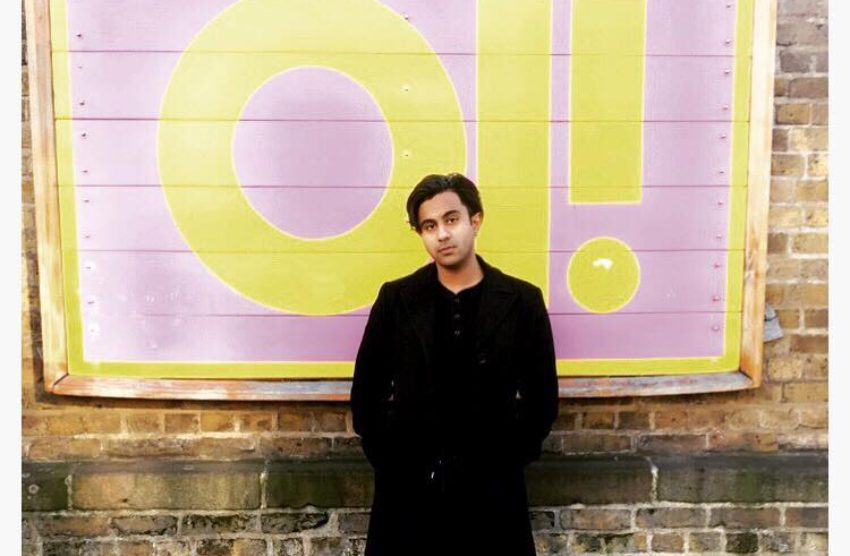 a male looking person wearing all black stands in front of a purple and yellow sign that read oi!