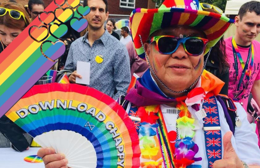 An elderly gay Malaysian man poses earring a rainbow-colored cowboy hat, floral necklace, and colorful cape, while holding a pride flag-themed fan
