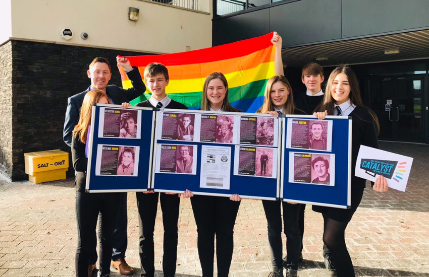 A group of six pupils post in front of a pride flag, holding a display of LGBTI history icons, both past and present