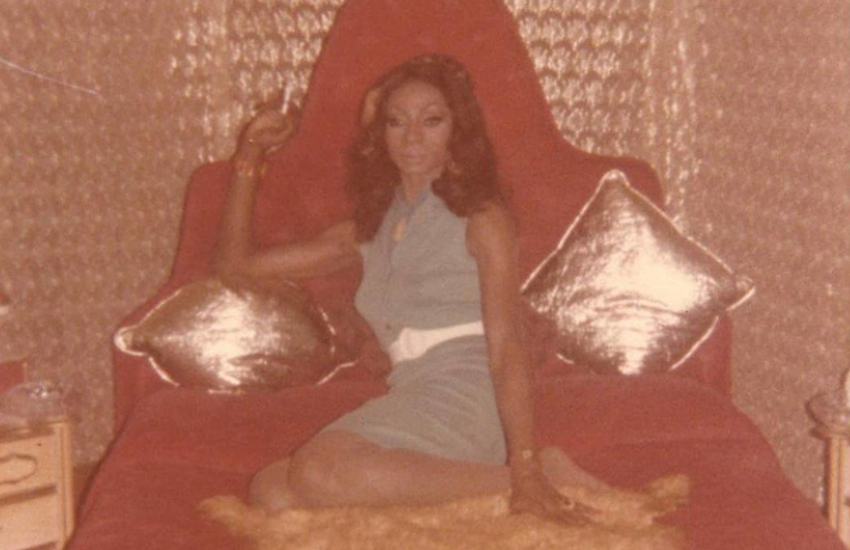 Singer Jackie Shane, lying leisurely and fabulously on a red couch between two metallic pillows