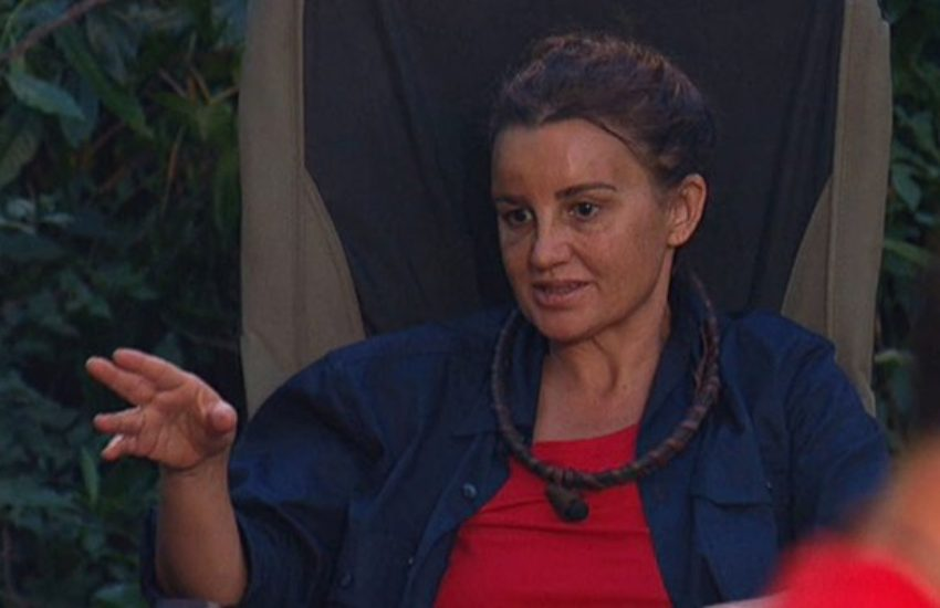 jacquie lambie sitting on a seat in the jungle in a red tshirt, she is talking and pointing her fingers