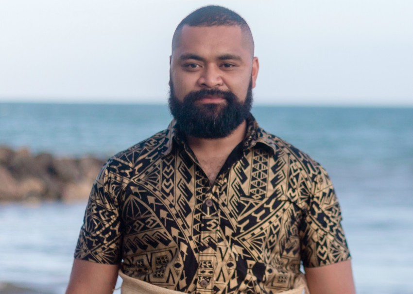 a man in traditional tongan clothes standing on a beach
