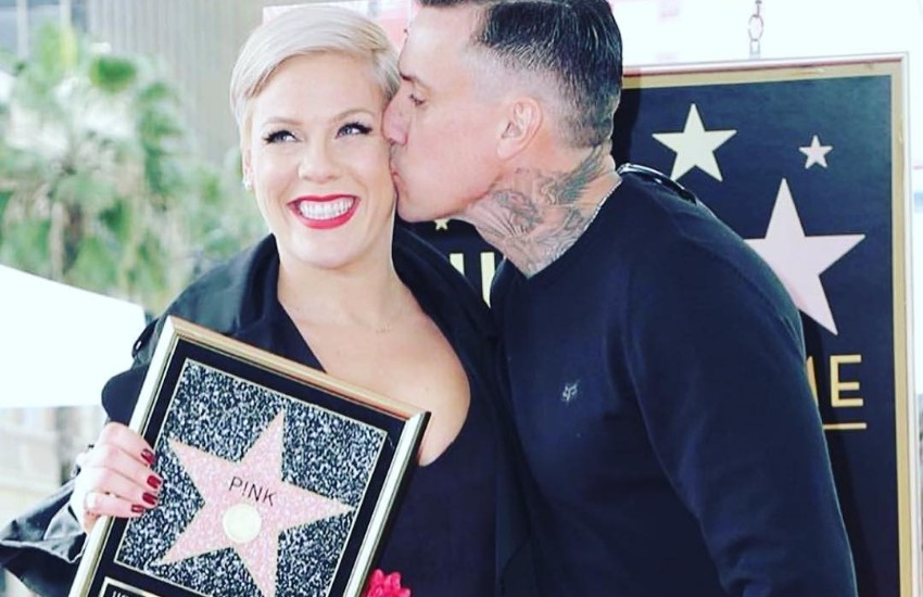 Pink receives a kiss from her husband while holding the plaque showing her Hollywood star