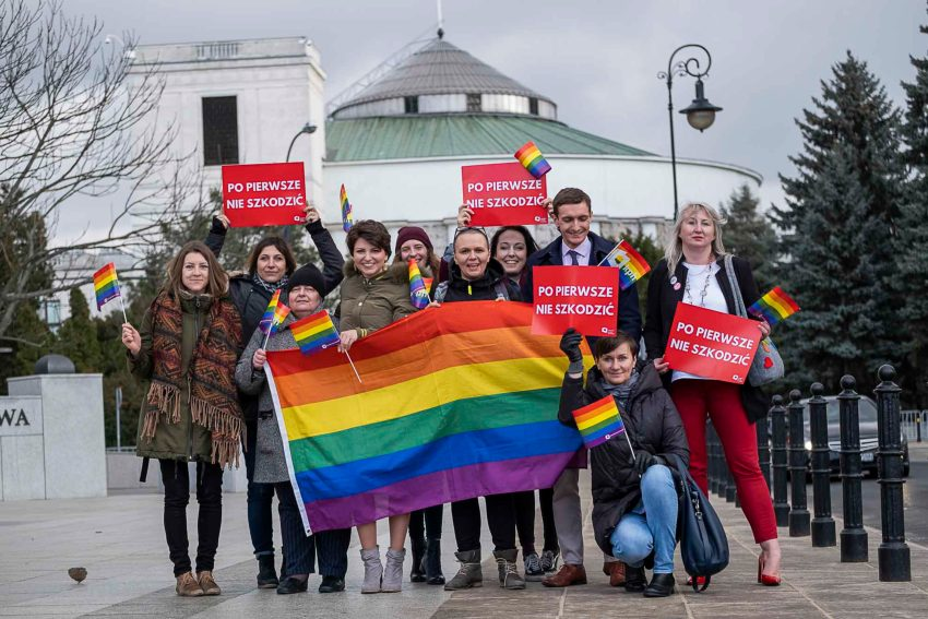 a group of people standing outside in a group, some are holding rainbow flags and red placards written in polish