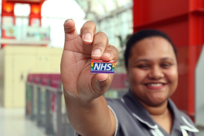 a woman holds a small badge with a rainbow flag that reads NHS close to the camera
