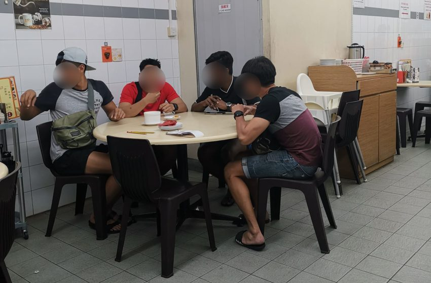 four men sitting a restaurant table, their faces are blurred