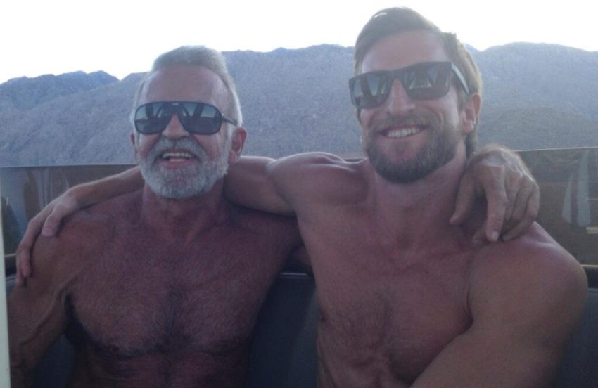 two men sit topless on a boat with their arms around each other's shoulders, they are wearing sunglasses and smiling