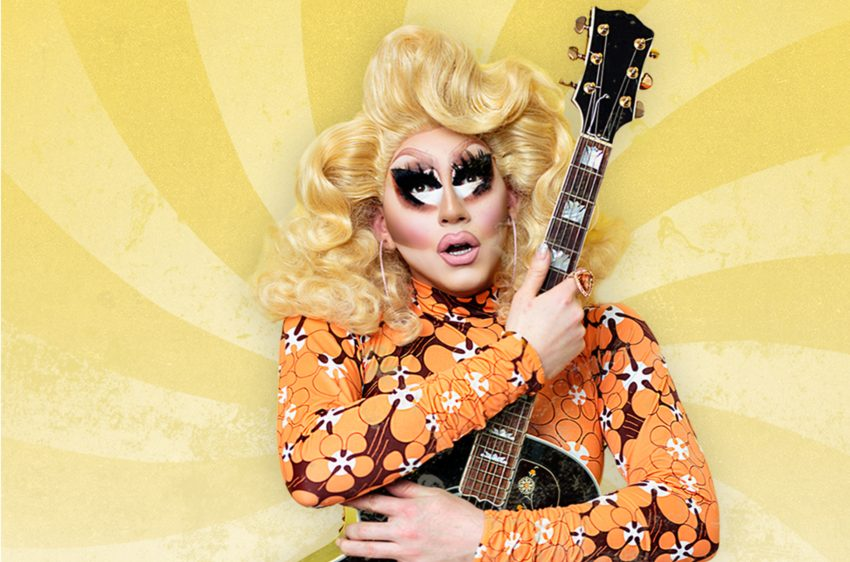 a press shot of trixie is standing in front of a psychedlic yellow background she is holding a guitar upright to her chest