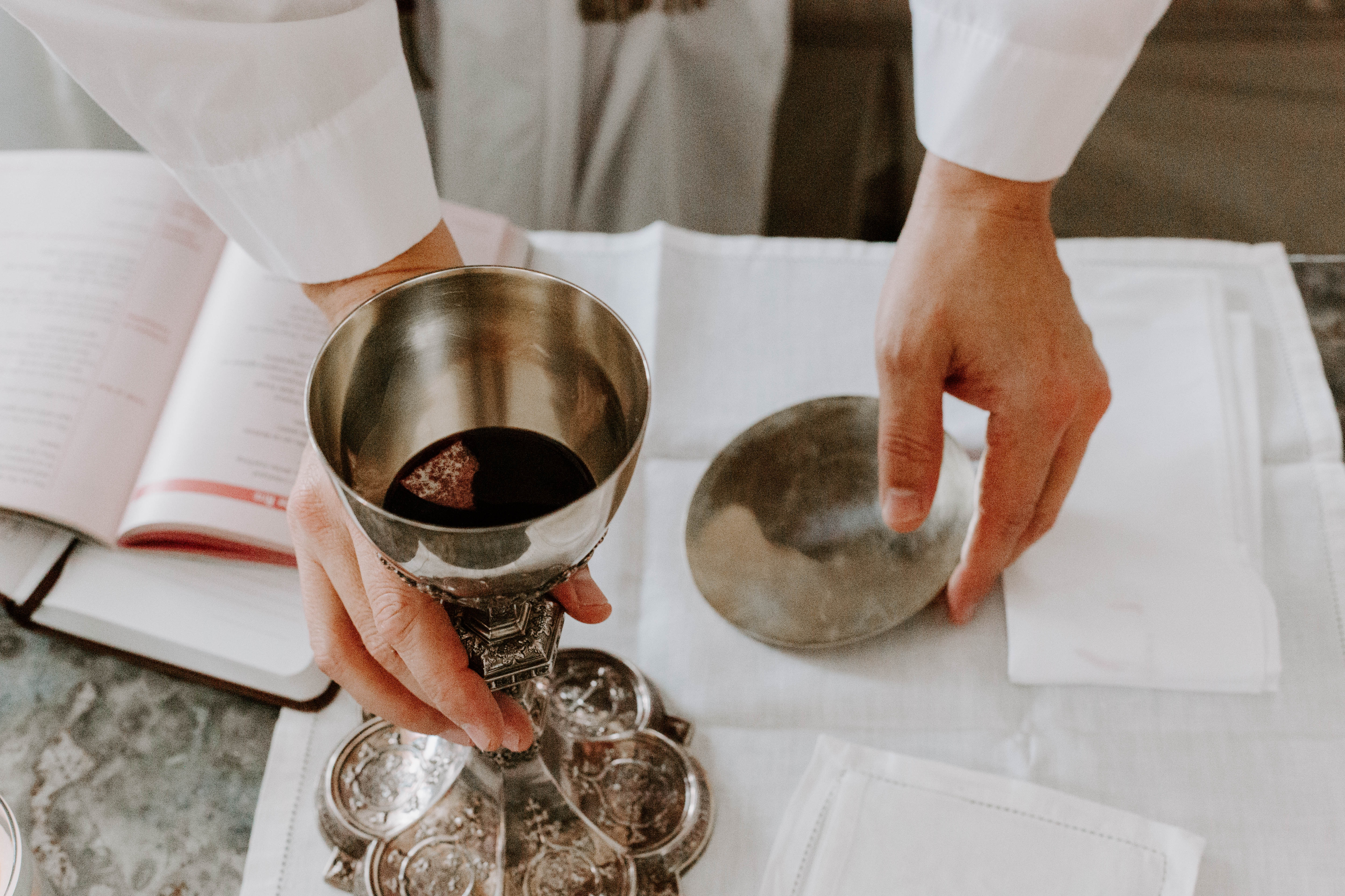 A priest holding a metal glass of Communion wine