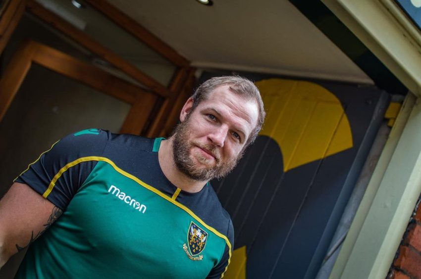an angle shot of james haskell who is looking at the camera smiling and wearing his rugby kit