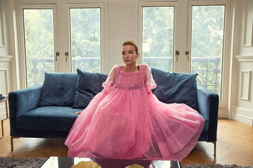 a woman in a pink fluffy dress sitting on a couch