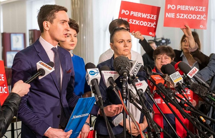 people standing behind reporter's microphones while people holding red placards with words written in polish standing behind them in Poland