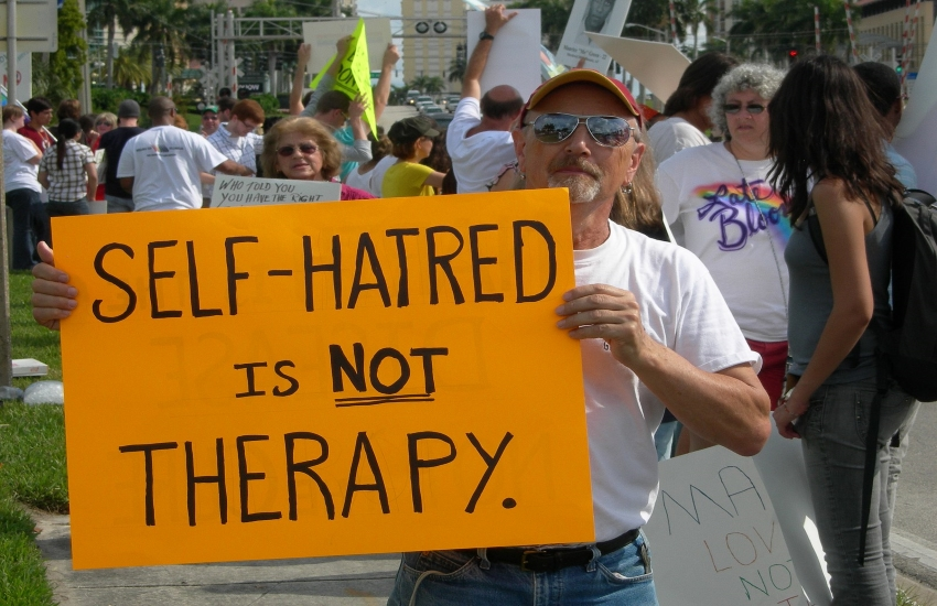 A protest sign reading 'Self-hatred is NOT therapy.' (Photo from Wikimedia Commons)