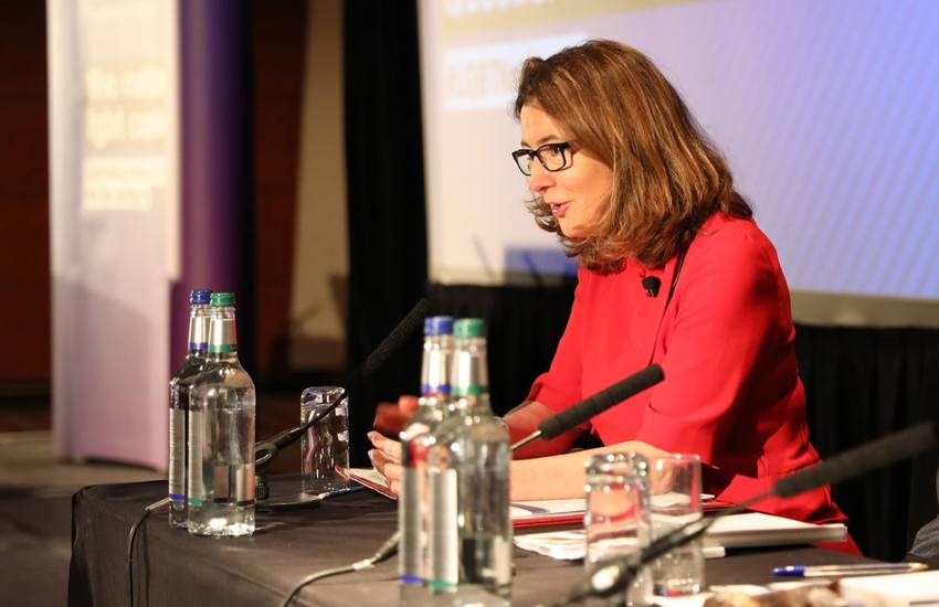 baroness Williams sitting at a desk talking into a microphone