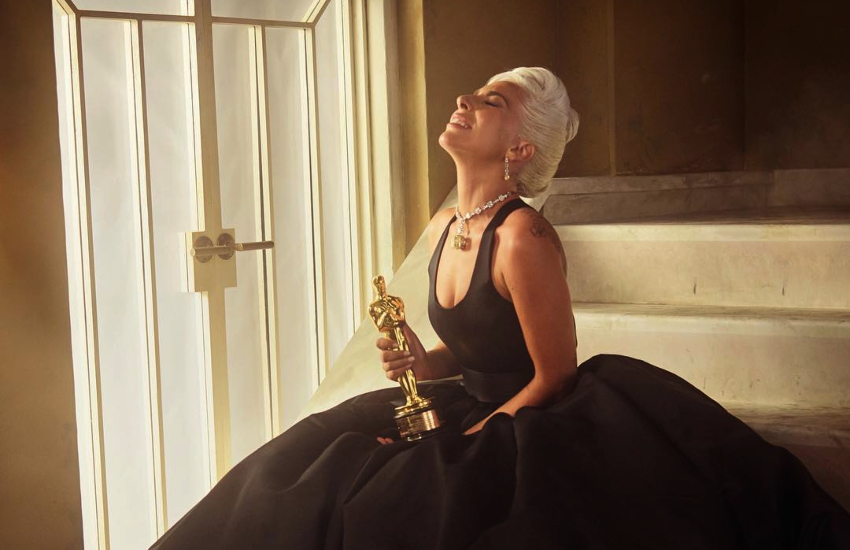 Lady Gaga holds her Grammy award in a billowing black gown
