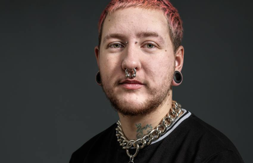 a professional shot of a LGBTI man who has short pink hair and lots of piercings on his face and ears