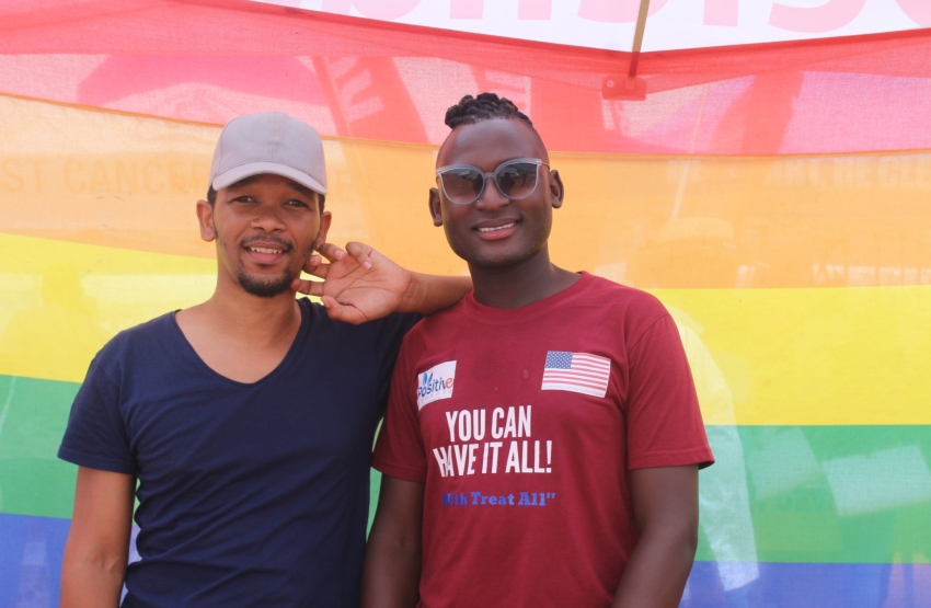 two men stand in front of a large rainbow pride flag in Botswana