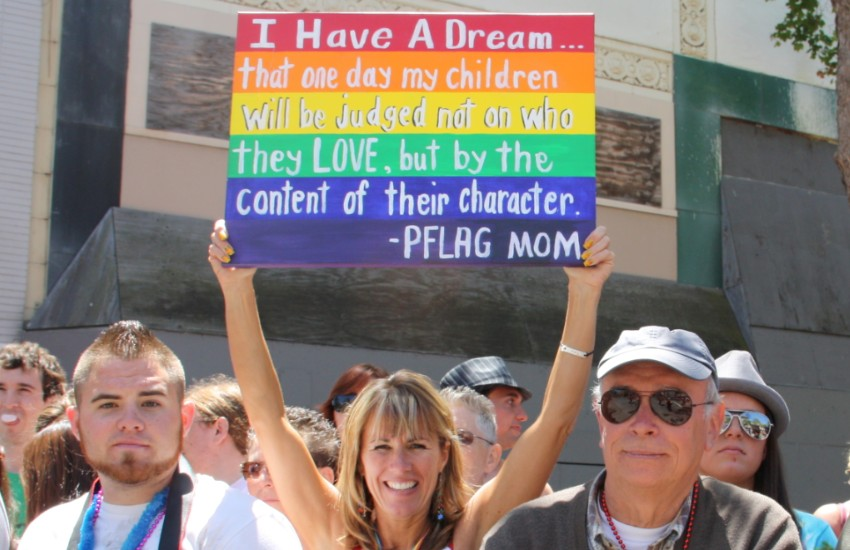 A mom holds up a sign for her LGBTI kids at Pride