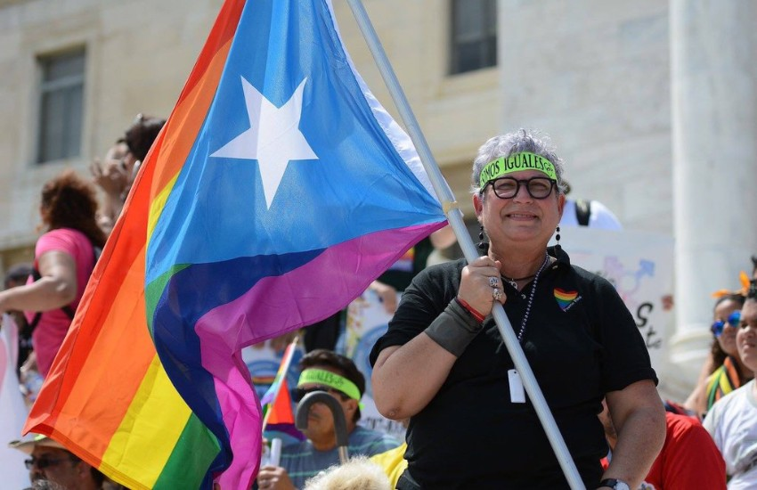 A person carries a rainbow flag for Puerto Rico at a march