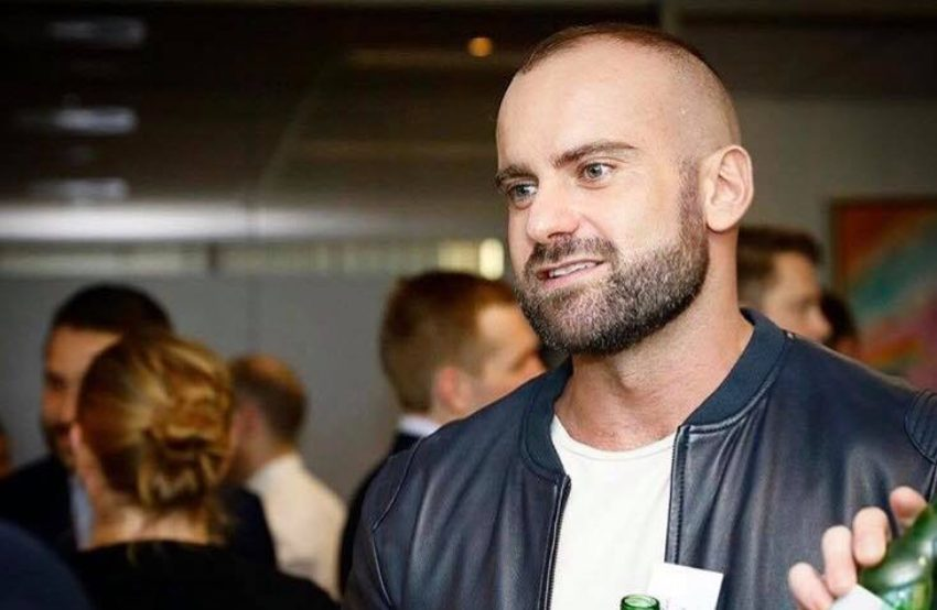 Rad mitic standing at an event talking to another person his hair is short and he is wearing a light leather jacket over a white t-shirt