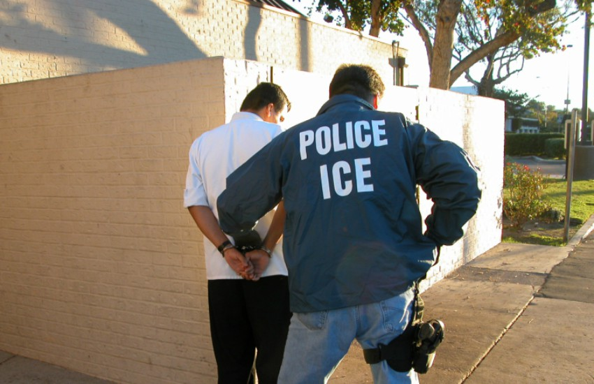 A U.S. Immigration and Customs Enforcement agent arresting an alleged suspect