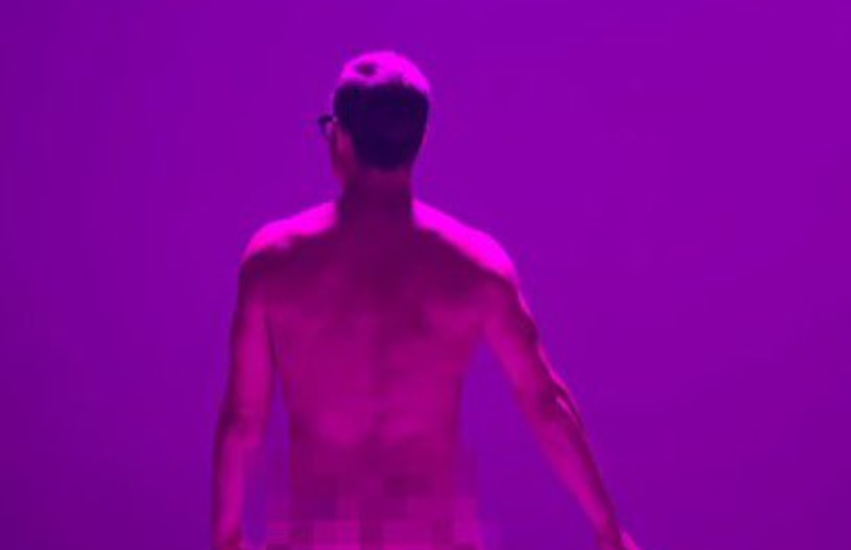 a naked will young stands with his back to the camera. he is shot in pink light and facing a purple background