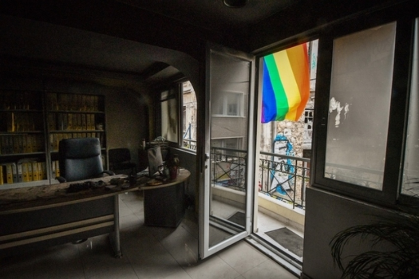 inside a burnt office, the camera faces the balcony which shows a bright rainbow flag waving