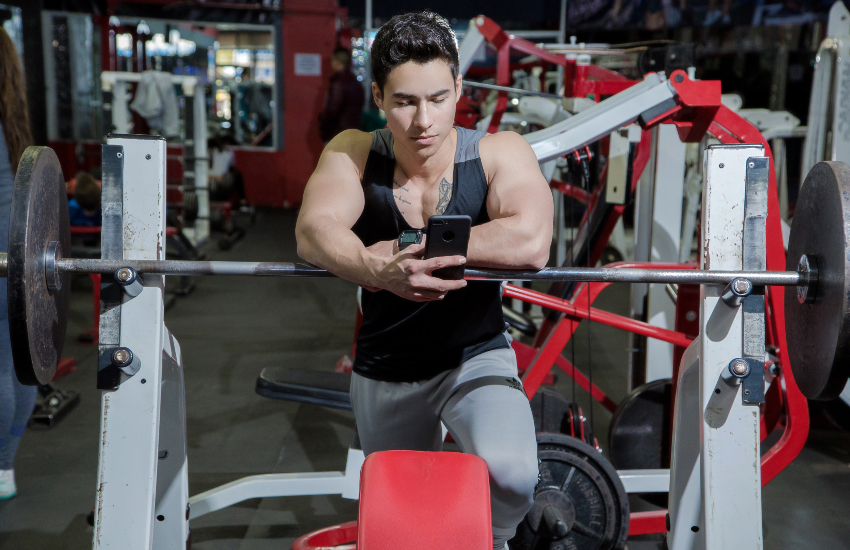 Muscular model posing at the gym, holding his phone