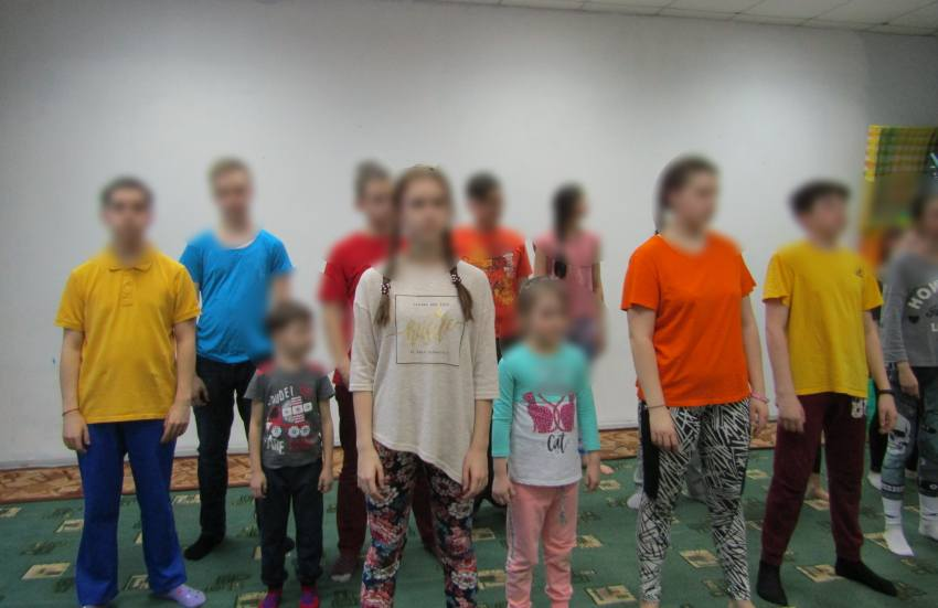 a group of children stand in a room of all different ages. their faces are blurred